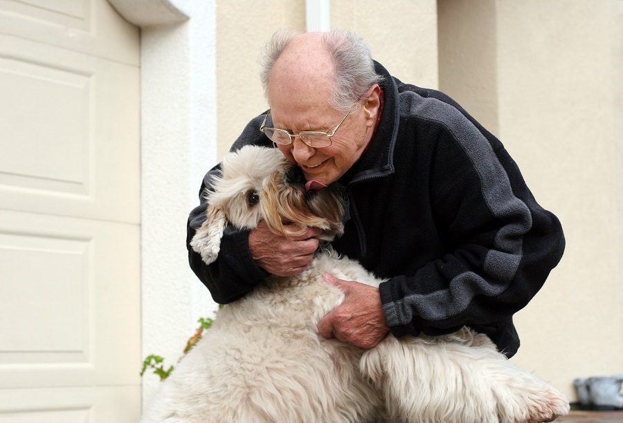 An senior man hugging his dog