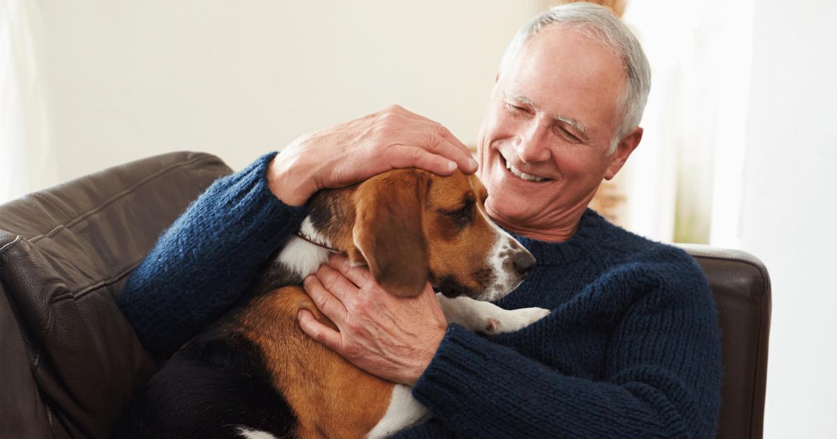 Smiling Senior Man patting dog in Aged Care